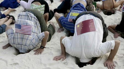 Các nhà hoạt động vì môi trường ở Cancun mặc áo có dán hình quốc kỳ các nước, đâm đầu vào cát để biểu thị việc các nước nhắm mắt làm ngơ trước hậu quả của biến đổi khí hậu - Ảnh: Reuters